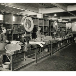 Workers cutting and weighing processed rubber